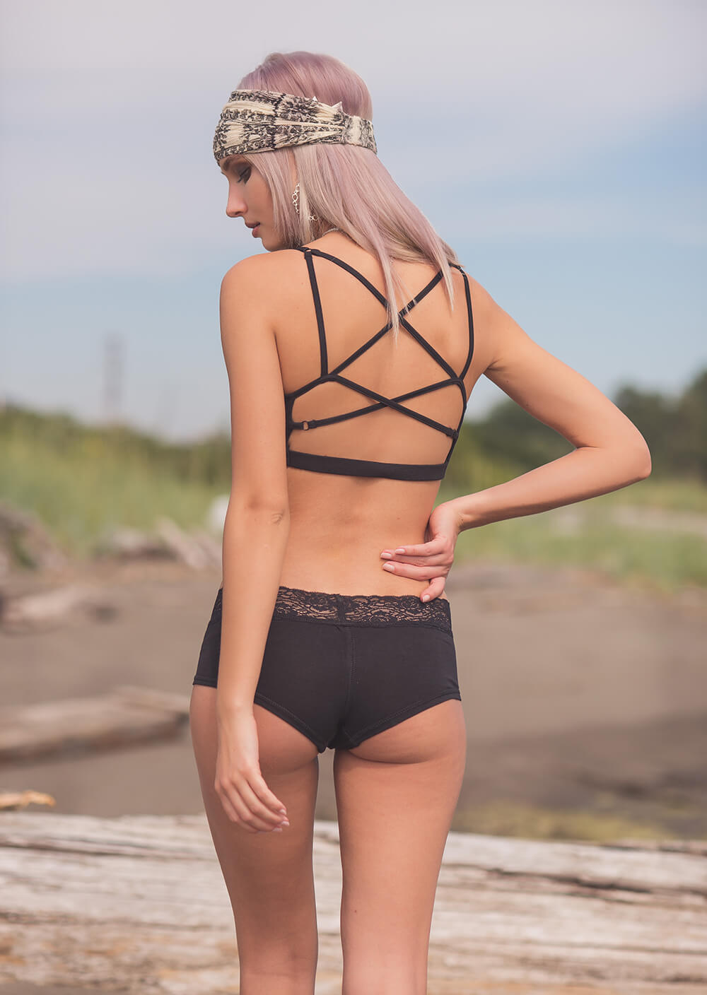 Model facing away wearing Nomads Hemp Wear organic cotton and bamboo Temptation bra, with criss cross adjustable straps.